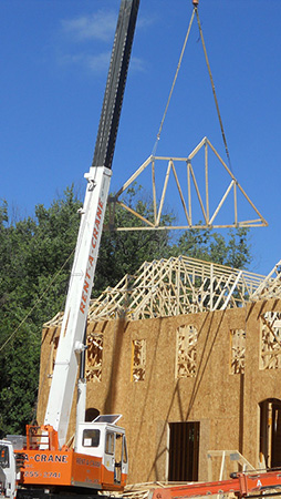 a crane lifts a piece of framing above a home under construction.