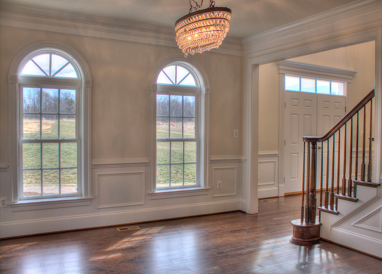 Dining Room with two windows with arch tops and chandelier.