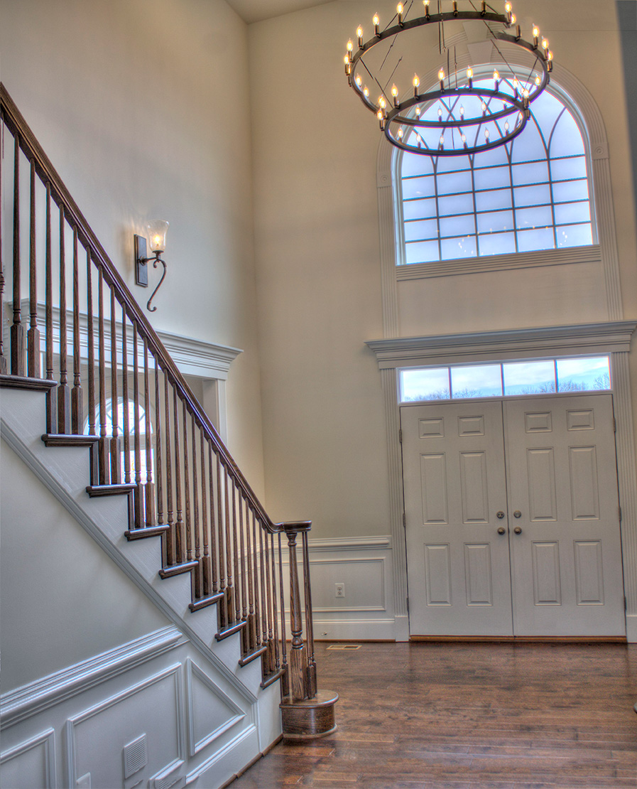 Looking past stairs into two-story foyer with chandelier and palladium window.