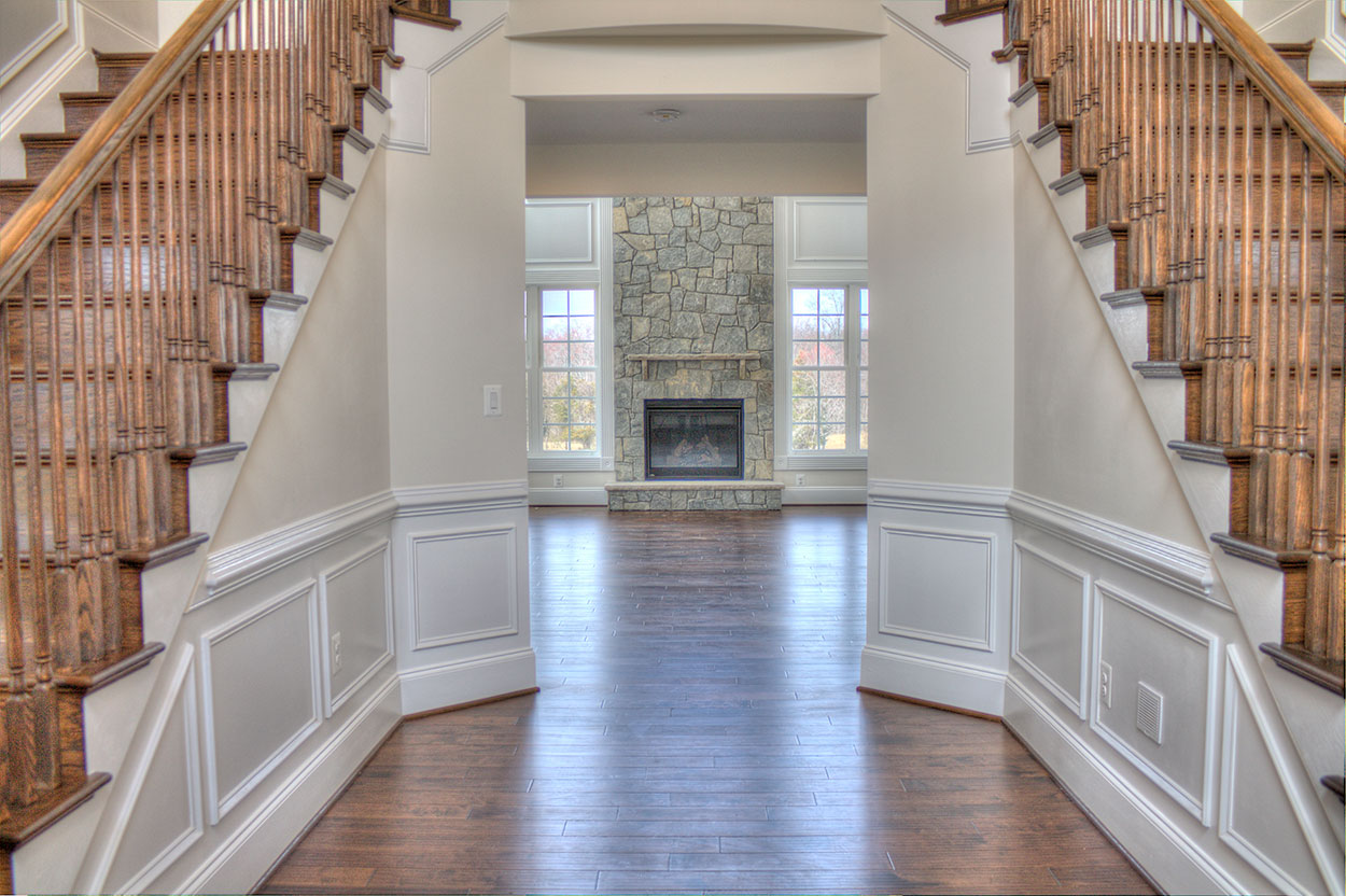 Looking into the Family Room from the Foyer, between staircases, fireplace in distance.